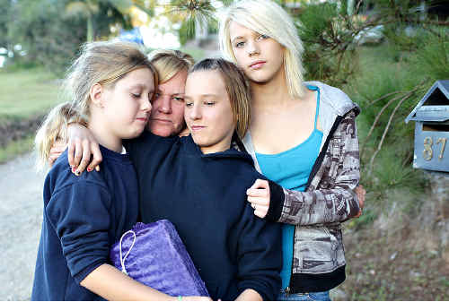 FAMILY PAIN: Davina Clark cuddles her children Chloe (left), Aleesh (second right) and Jessica, as they hold their grandfather David Smart's ashes yesterday.